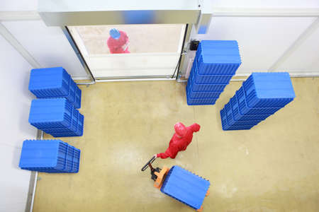 controling: goods delivery in storehouse - overhead view of two workers working in small warehouse