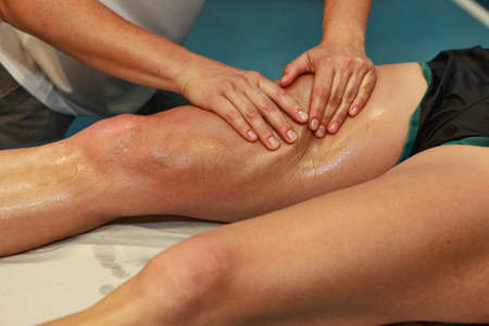 masaje: manos masajeando el muslo atleta s después de correr