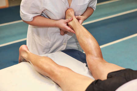 treat acupressure: masseuse massaging athlete s Achilles tendon after running Stock Photo