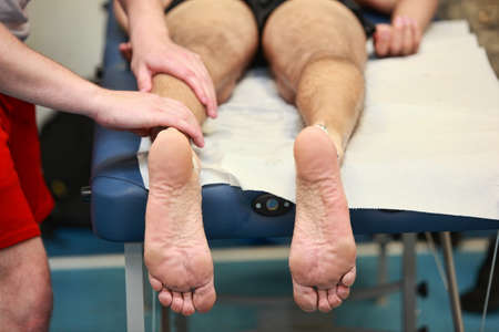treat acupressure: runner s feet, masseur  massaging athlete s leg muscles after running