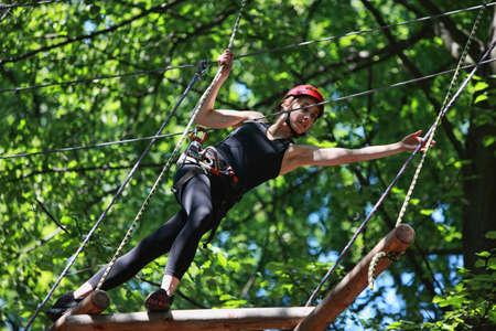 Junge kaukasisch attraktive Frau Klettern im Seilpark in Berg Helm und Sicherheitsausrüstung