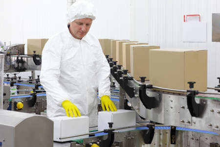 packing: caucasian  worker in apron, cap at production line in factory Stock Photo