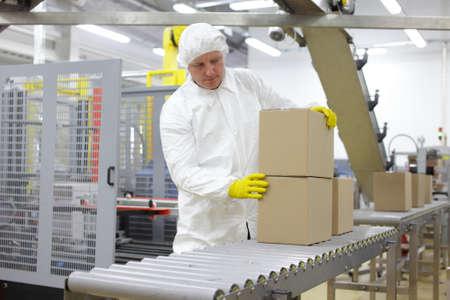 工場内梱包ラインで白いエプロンの白人の労働者