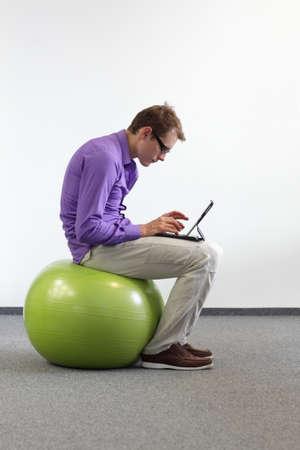 malos habitos: hombre con la tableta en la bola grande de la estabilidad - mala postura al sentarse