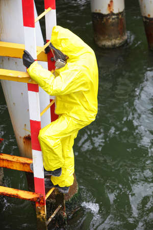sea dock:  worker in protective suit  climbing ladder over the sea Stock Photo