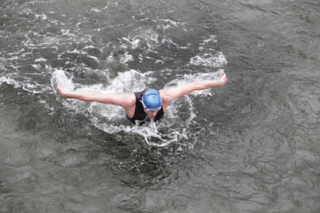 dynamic and fit swimmer in cap and wetsuit breathing performing the butterfly stroke in dark ocean water stroke in dark ocean water photo