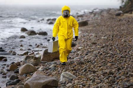 contaminacion del agua: especialista en traje de protección con la maleta de plata caminando en la playa rocosa en día de tormenta Foto de archivo