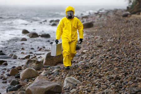 risk taking: specialist in protective suit with silver suitcase walking on rocky beach in stormy day Stock Photo