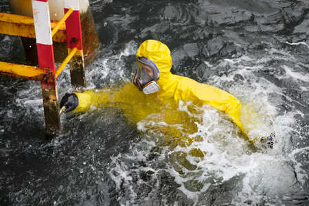 protective suit: worker in professional, protective suit in ocean water  trying to reach  ladder to save his life  Stock Photo