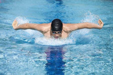 techniek: dynamisch en fit zwemmer in cap ademhaling die de vlinderslag in het zwembad