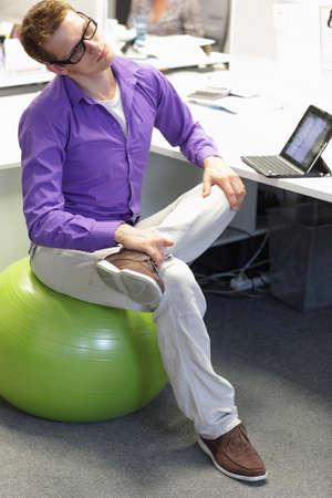 ufficio aziendale: uomo sulla sfera di stabilit� con pausa per l'esercizio in lavoro d'ufficio