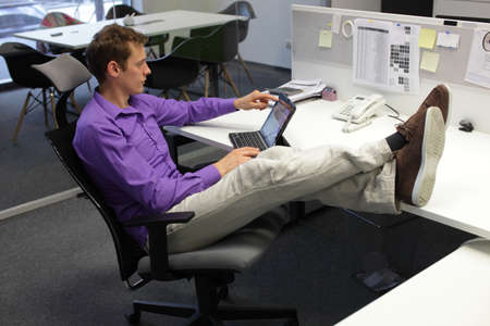 Young businessman caucasian in his office working with tablet - relaxed sitting position with legs on desk photo