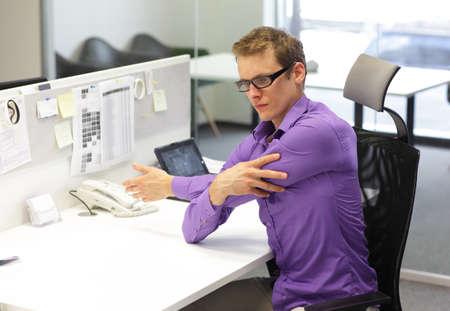 trabajadores: oficinista masculina, hacer ejercicio durante el trabajo con la tableta en su escritorio
