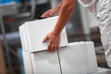 Arbeiter am Fließband, die sich mit Boxen in der Fabrik Lizenzfreie Bilder
