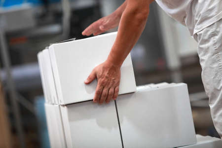 white box: Manual worker at production line dealing with boxes in factory Stock Photo