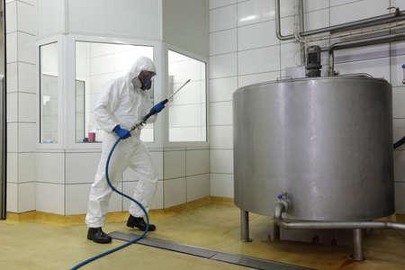the handle: trabajador en uniforme de protección blanca, máscara, guantes con lavadora de alta presión en gran tanque de proceso industrial que se prepara para la limpieza Foto de archivo