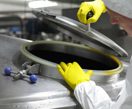 hands in yellow gloves opening industrial process tank - close up  photo