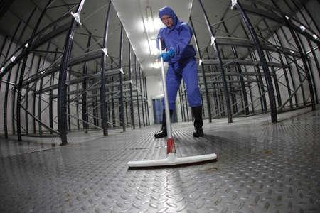trabajador en azul piso de la limpieza, de protección uniforme en almacén vacío - lente ojo de pez