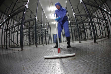 cleaning equipment: worker in blue, protective  uniform cleaning floor in empty storehouse - fish eye lens