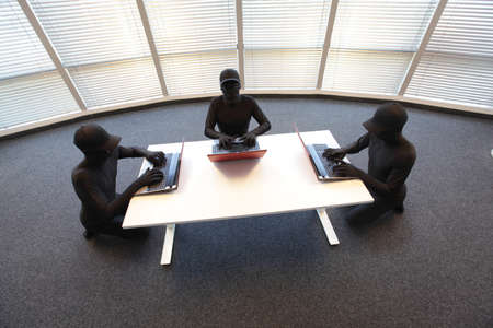 group of anonymous hackers in black costumes working with computers in office photo