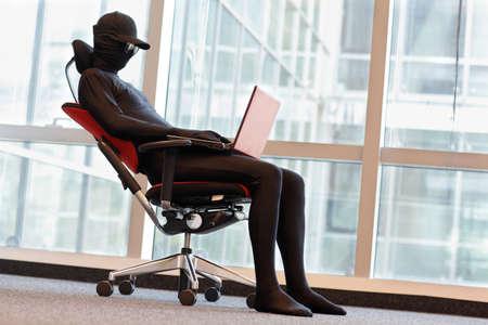 オフィスのラップトップで働くプロの匿名ハッカー