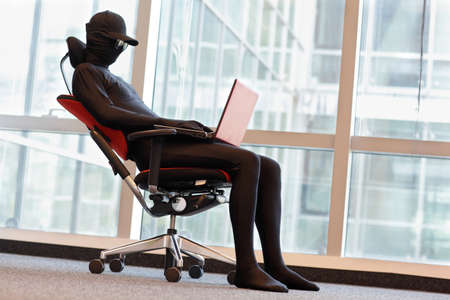 professional anonymous hacker working with laptop in office