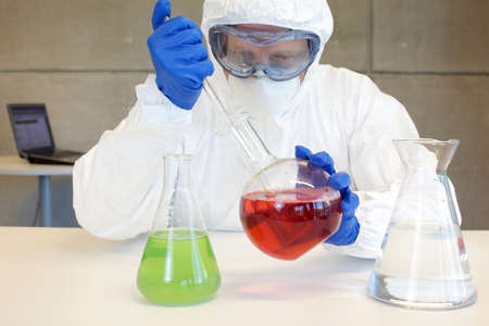 technician in protective uniform working with toxic substance in lab photo