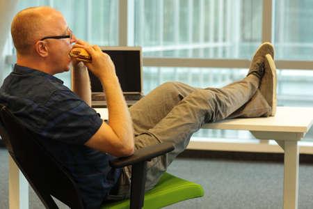 中年白人の男、デスクでのリラックスした位置に座っている彼のオフィスでハンバーガーを食べる
