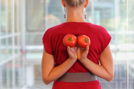 lycopene: fit business woman with tomatoes as a healhy snack - back view