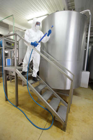 welly: worker in white protective uniform,mask,gloves with high pressure washer on stairs at large industrial process tank preparing to cleaning Stock Photo
