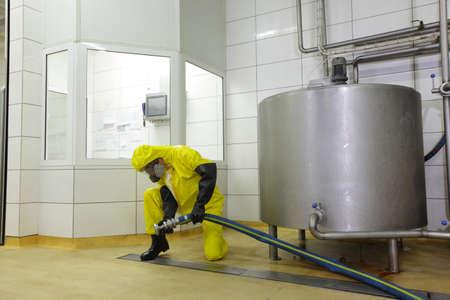 técnico totalmente protegida con el uniforme amarillo, trabajando con gran manguera al tanque grande de plata en fábrica Foto de archivo