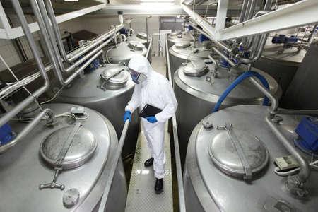 Técnico en uniforme protector y máscara con la tableta controlar el proceso tecnológico en la planta de Foto de archivo
