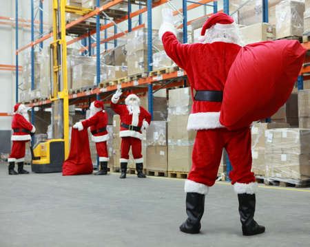 Group of santa clauses working together in storehouse with gifts
