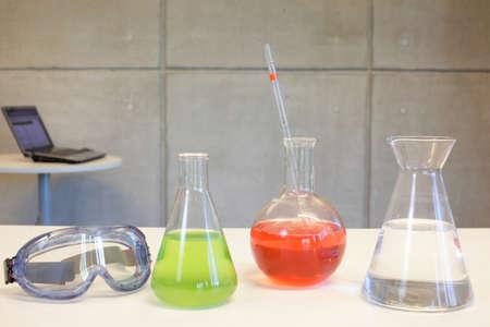 glassware,goggles on desk in laboratory,laptop in background photo