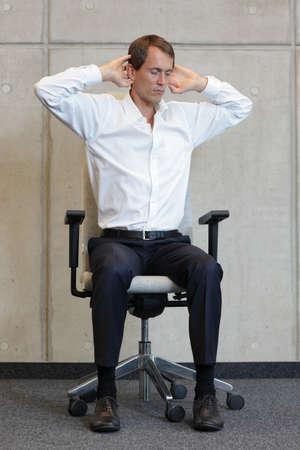 silla: Hombre de negocios en el ejercicio de la silla - la prevenci�n de enfermedades ocupacionales oficina Foto de archivo