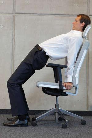 disease prevention: Hombre de negocios en el ejercicio de la silla - la prevenci�n de enfermedades ocupacionales oficina Foto de archivo