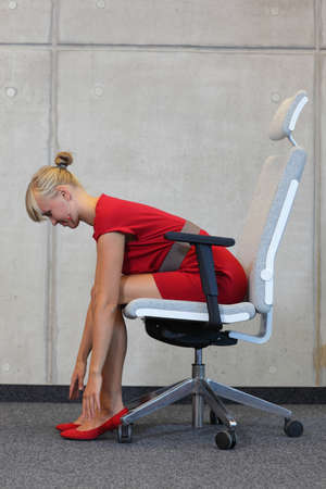 disease prevention: office occupational disease prevention - business woman exercising on chair