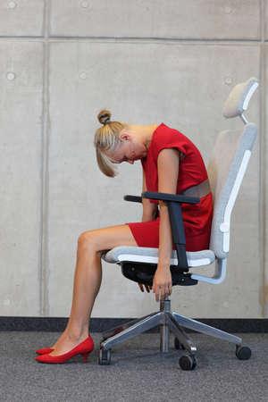 mujer trabajadora: Mujer de negocios en el ejercicio de la silla - la prevenci�n de enfermedades ocupacionales oficina Foto de archivo