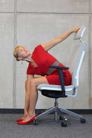 break at work in office - relax on chair  - business woman exercising photo