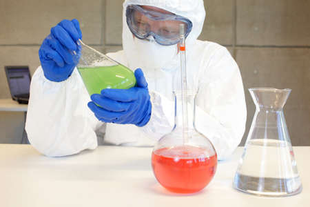 technician in protective uniform working with chemicals in glassware  in lab photo