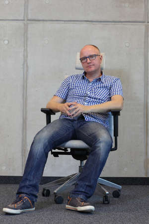 improper: middle-aged cauaciasn man wrong sitting posture on  office chair