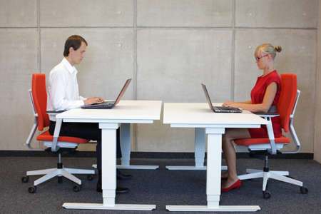 business man and woman working in correct sitting posture with laptops  at electric  height adjustable desks in office Banque d'images