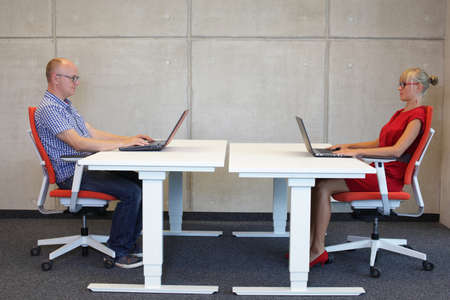 office: middle-aged man and young woman working in correct sitting posture with laptops  at electric height adjustable desks in office Stock Photo