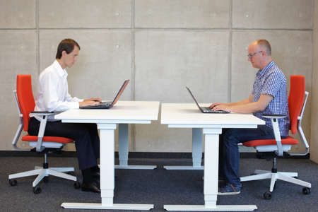 two men working in correct sitting posture with laptops  at electric height adjustable desks in office