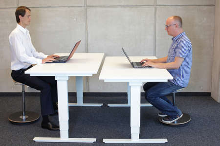 two men working in correct sitting posture on pneumatic leaning seats  with laptops  at electric height adjustable desks in office