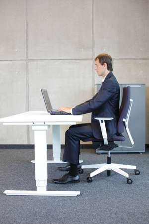 워크 스테이션에서 올바른 앉은 자세. 그의 사무실에서 노트북을 사용하는 안락 소송에서 비즈니스 사람 (남자)