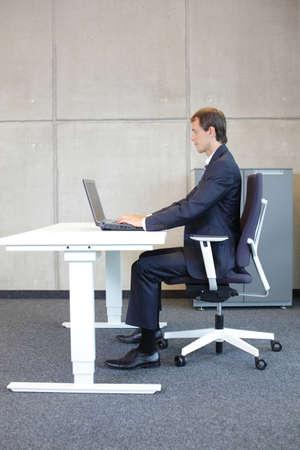 richtige Sitzposition an der Arbeitsstation. Geschäftsmann in der Klage, die auf Lehnsessel arbeitet mit Laptop in seinem Büro