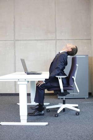 disease prevention: Hombre de negocios en el ejercicio de la estaci�n de trabajo - la prevenci�n de enfermedades ocupacionales Oficina