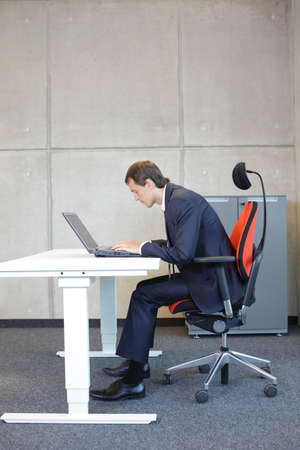 office cabinet: Bad sitting posture at laptop .short-sighted business man in suit on armchair in his office