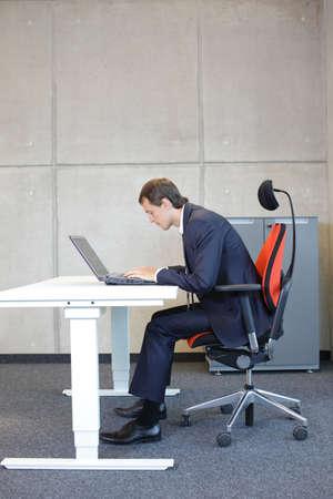 Bad Sitzhaltung am Laptop .Kurze schauende Geschäftsmann in der Klage auf Sessel in seinem Büro